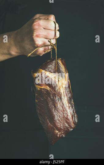 Man' s hand holding cut of cured pork meat at local farmers market, black background. Gourmet, organic food - Stock Image