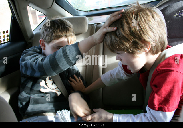 two brothers fighting with eachother in the back seat of car - Stock-Bilder