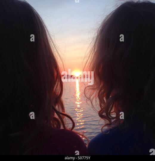 Two siblings gazing at the midnight sun in the north of Finland - Stock Image