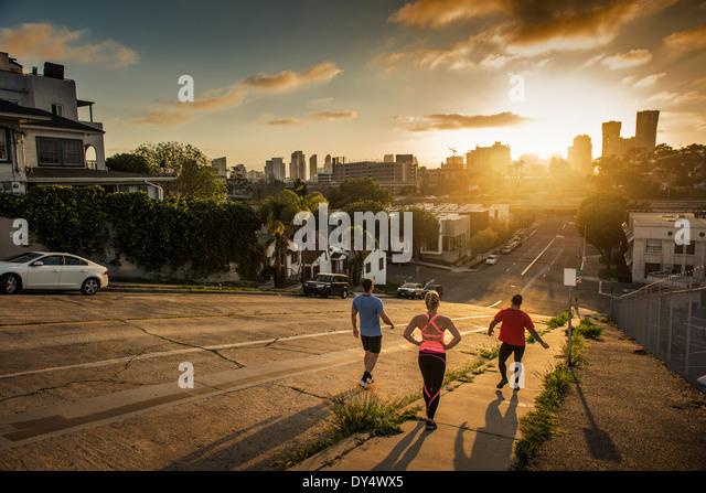 Team of runners running down a steep city hill - Stock-Bilder