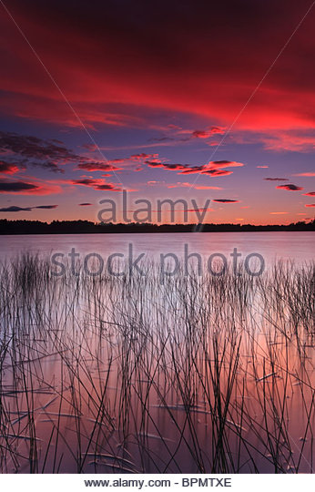 Colorful skies at dusk, at Huggenes in the lake Vansjø, Rygge kommune, Østfold fylke, Norway. - Stock-Bilder