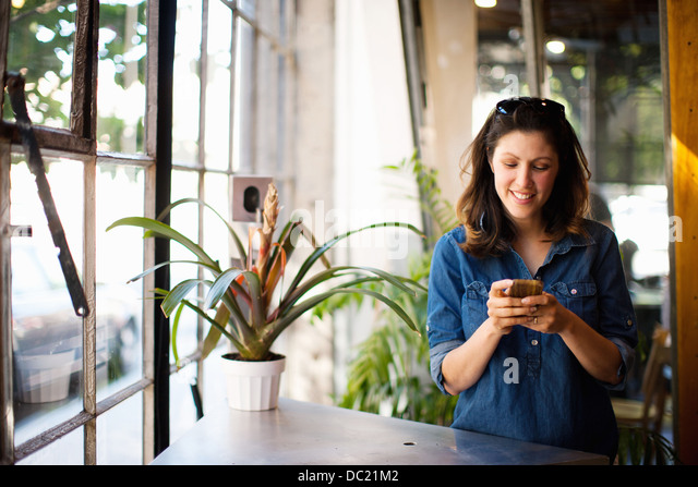 Mid adult woman using cellphone indoors, smiling - Stock Image