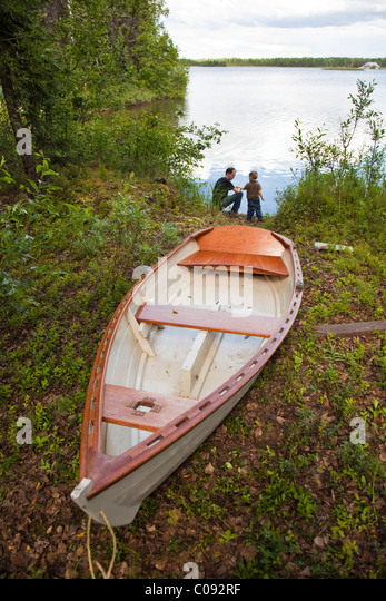 Father kneels next to his toddler son on the shore of Willow Lake with a small wooden boat in the foreground, Mat - Stock Image
