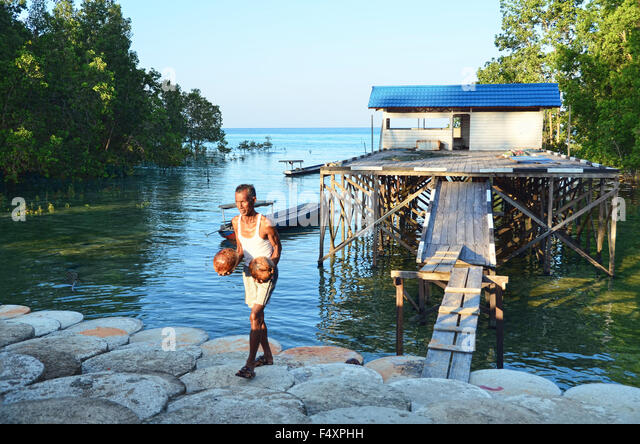 A man carrying two coconuts from a stilt house by the beach - Stock Image