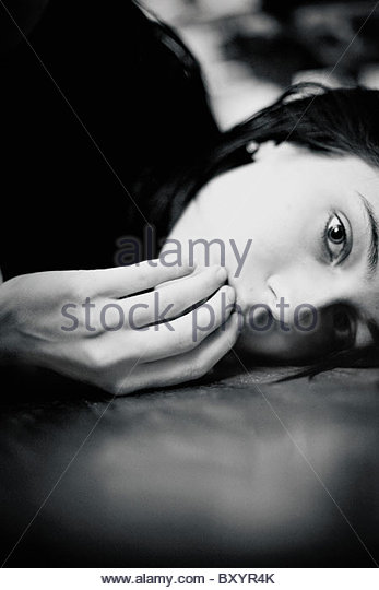 A teenage girl covering her mouth while lying down with apprehensive expression - Stock Image