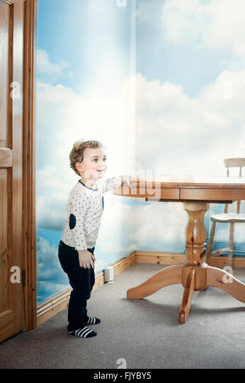 small boy playing around the wooden table in the kitchen - Stock Image