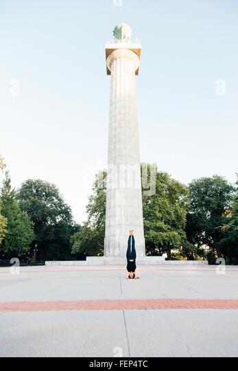 Woman doing headstand (Salamba Sirsasana), Prison Ship Martyrs' Monument, Fort Greene Park, New York, USA - Stock-Bilder