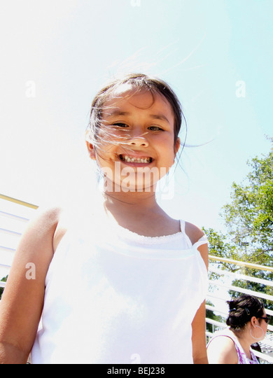 Young girl standing in bleachers smiling - Stock-Bilder