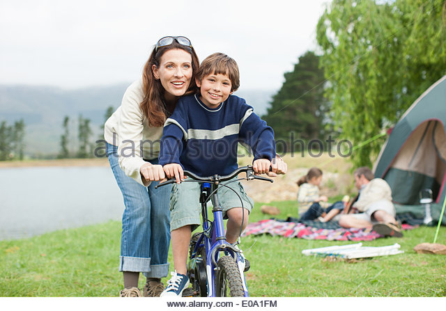Boy on bicycle while on family camping trip - Stock Image