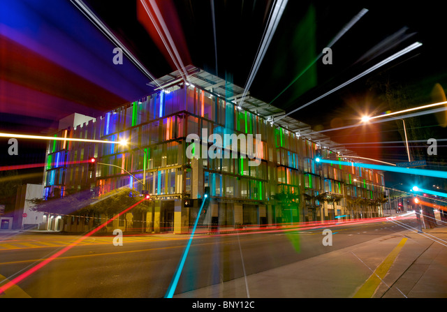 Streaked Light From a Colorful Lit Parking Garage at Night - Stock Image