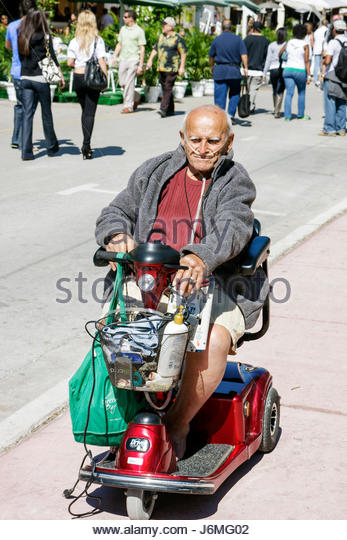 Miami Beach Florida Ocean Drive senior man electric wheelchair scooter cart oxygen disabled - Stock Image