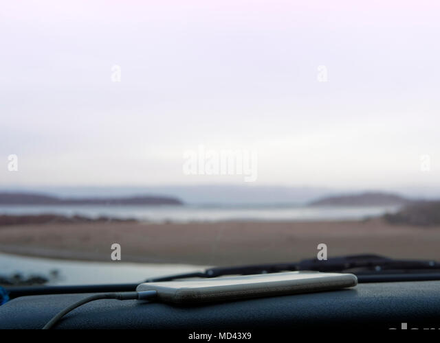 Smartphone on car dashboard, coastal view seen through car windscreen, Broulee, New South Wales, Australia - Stock Image