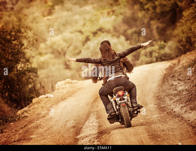 Sporty family traveling on motorbike, riding on motorcycle with raised up hands, active people, extreme sport, freedom - Stock Image