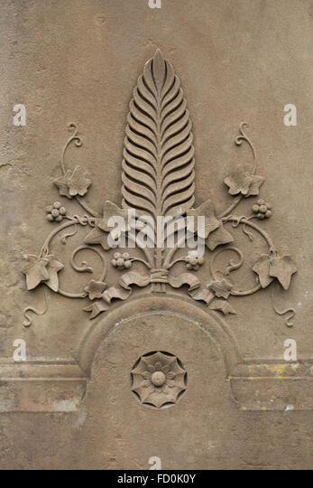 Palm leaf surrounded by ivy. Detail of a tombstone in the churchyard in Creglingen, Baden-Wurttemberg, Germany. - Stock Image