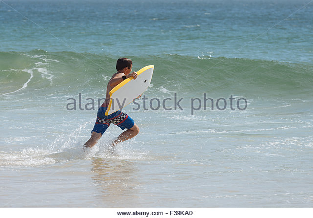 Teenage boy running in the surf holding a boogie board - Stock Image