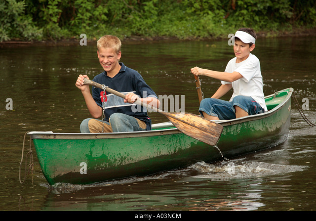 two young boys in a canoe - Stock Image
