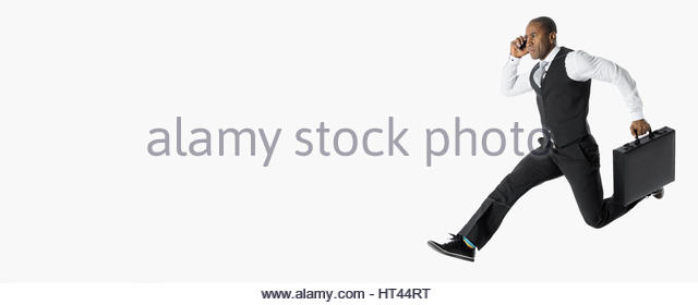 Energetic businessman running and jumping, talking on cell phone against white background - Stock-Bilder