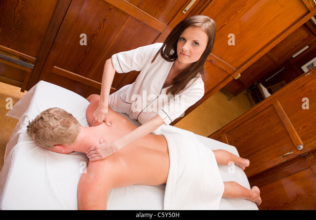 Overhead portrait of a massage therapist gives a massage in an old style spa - Stock Image
