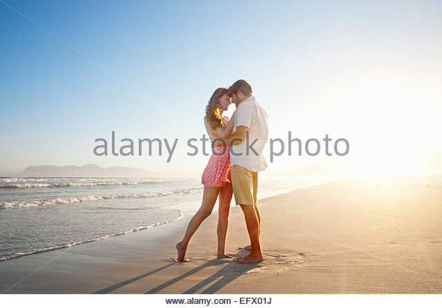 Romantic couple embracing, looking into each others eyes, on sunny beach - Stock Image
