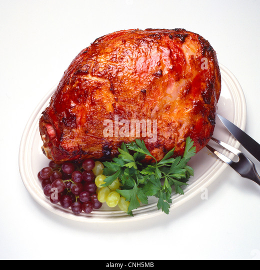 whole baked smoked ham with grapes garnish on platter - Stock Image