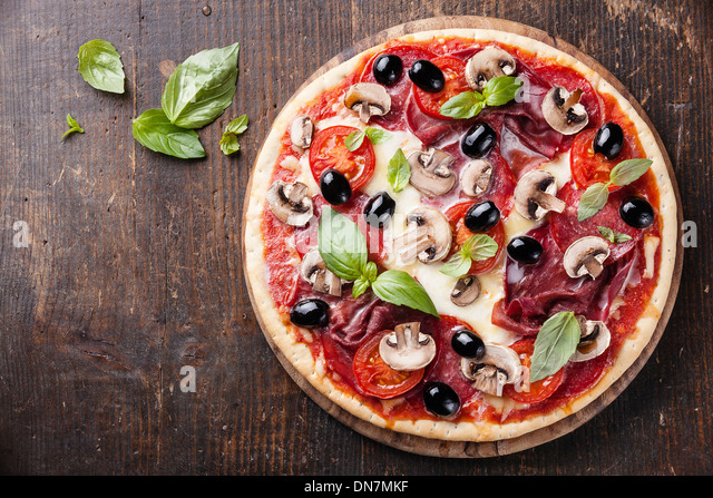 Italian pizza with salami, mushrooms and olives on wooden table - Stock Image