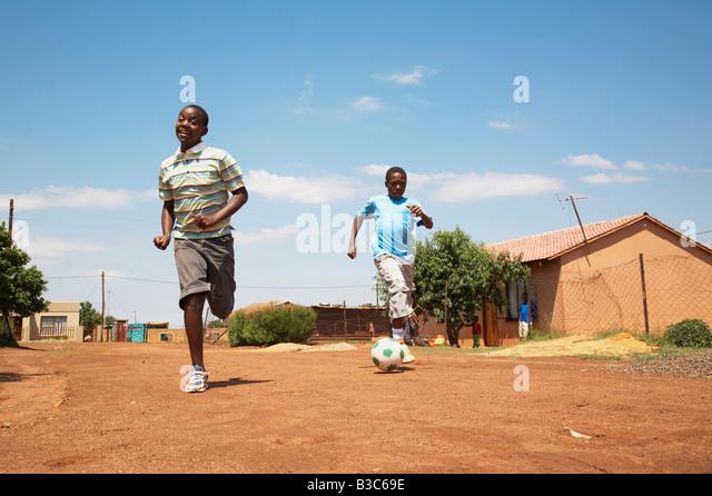 Township children playing soccer in the road.Orange Farm Gauteng MonkeyApple Stock Photography cc 2007 Released - Stock-Bilder