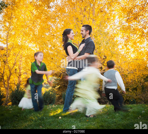 USA, Utah, Bountiful, Family with children (2-3, 4-5, 6-7, 8-9) dancing in garden at autumn - Stock-Bilder
