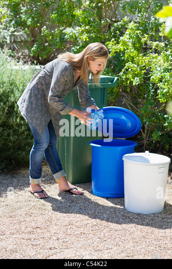 Woman throwing water bottles in garbage bin - Stock Image