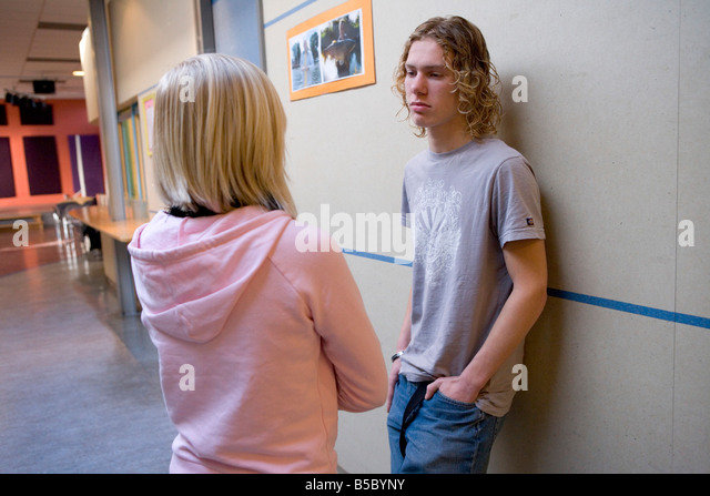 Teenage boy and girl talking in the school hall - Stock Image