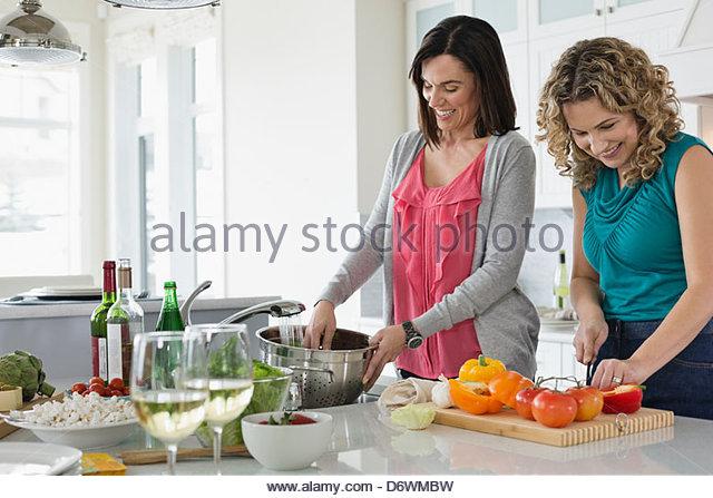 Happy mature women cooking together in kitchen - Stock-Bilder