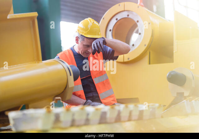 Tired steel worker in factory - Stock Image