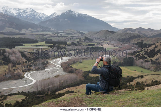 Traveler with backpack and binoculars sits on hill top. - Stock-Bilder