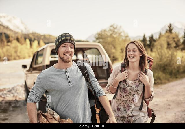 Young couple preparing to go hiking, carrying firewood, smiling - Stock-Bilder