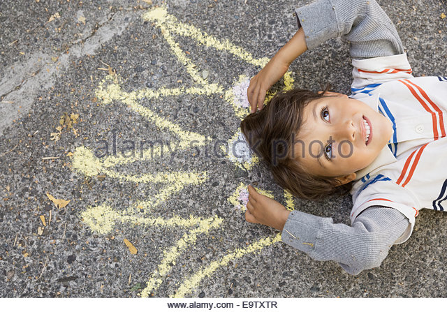 Curious boy with sidewalk chalk crown overhead - Stock Image