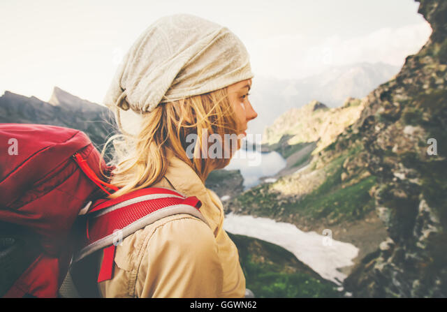 Young Woman with red backpack hiking alone Travel Lifestyle concept lake and mountains landscape on background Summer - Stock Image