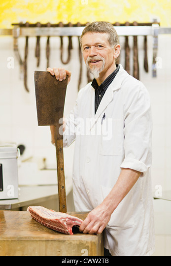 Butcher holding large knife and meat - Stock Image