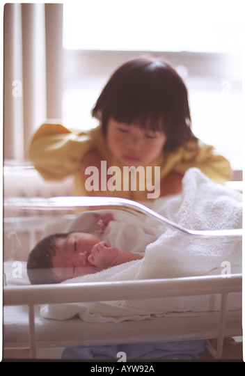 Girl looking into a new born baby - Stock-Bilder