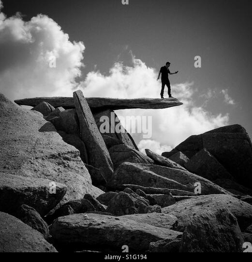 Climber on the Cantilever Stone on Glyder Fach, Snowdonia mountain range, Wales. - Stock-Bilder