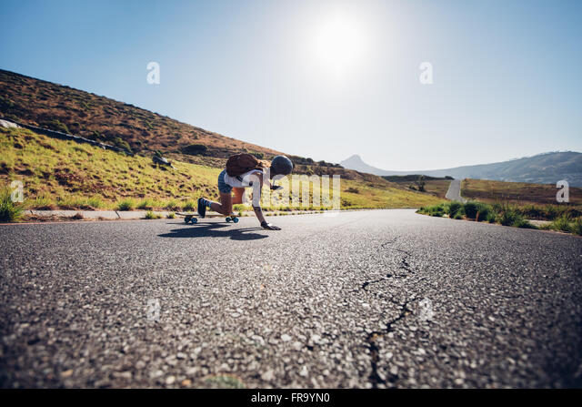 Rear view of young female skater practicing skateboarding on rural roads on a sunny day. She is doing stunts and - Stock Image