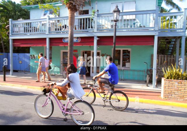 Florida Key West Florida Keys Bahamas Village Petronia Street man woman couple riding bicycles rental - Stock Image