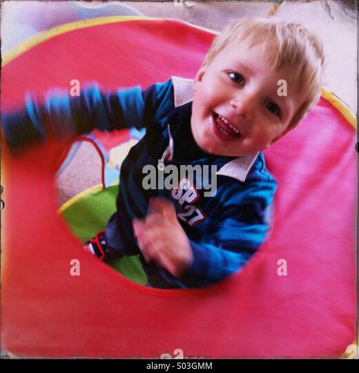 Young boy playing indoors in a small tent. Boy is about two years old. - Stock Image