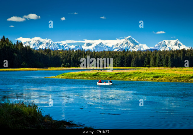 Two people canoeing down the Bartlett River with the Fairweather Range in the background, Glacier Bay National Park - Stock Image