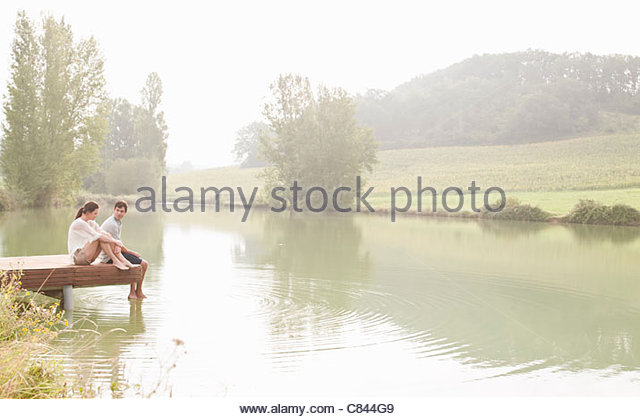 Couple relaxing on dock in lake - Stock Image
