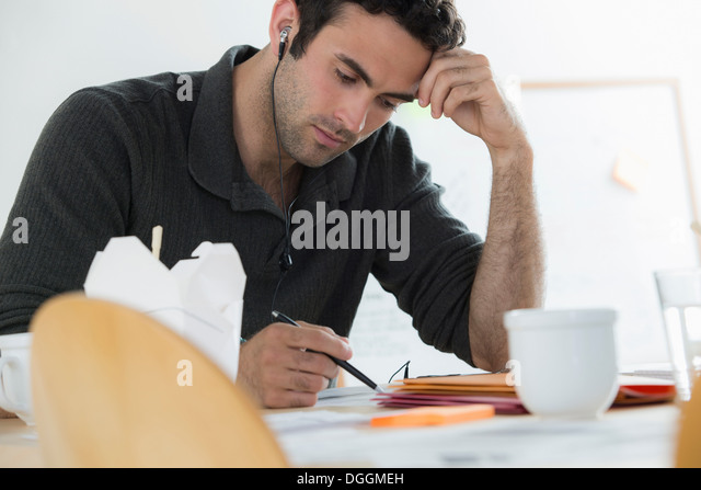 Portrait of male working through lunch - Stock Image
