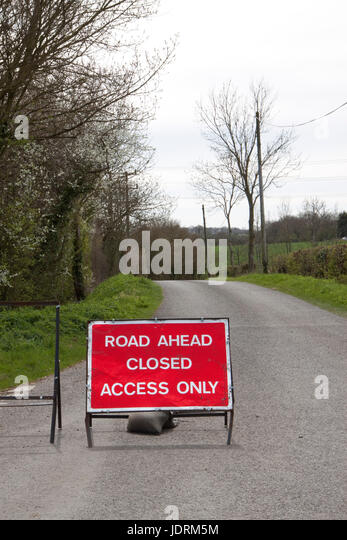 Read ROAD AHEAD CLOSED sign on a country road - Stock Image