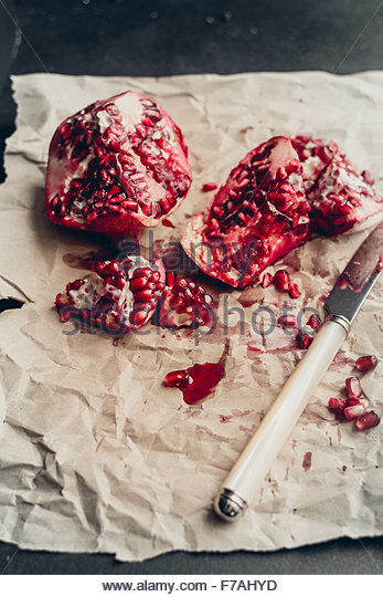 Pomegranates sitting on a wooden farm table with moody, dramatic light shining in from the left. Pomegranate seeds - Stock Image