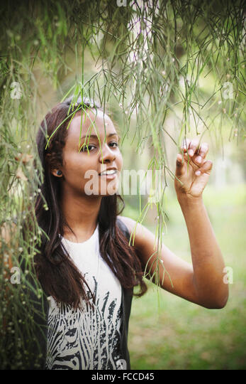Young Woman Holding Onto Willow Tree - Stock Image