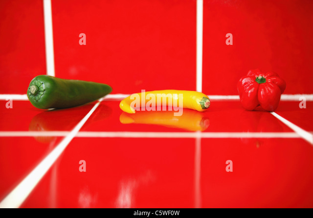 Bell pepper and chili pods on red tiles - Stock Image