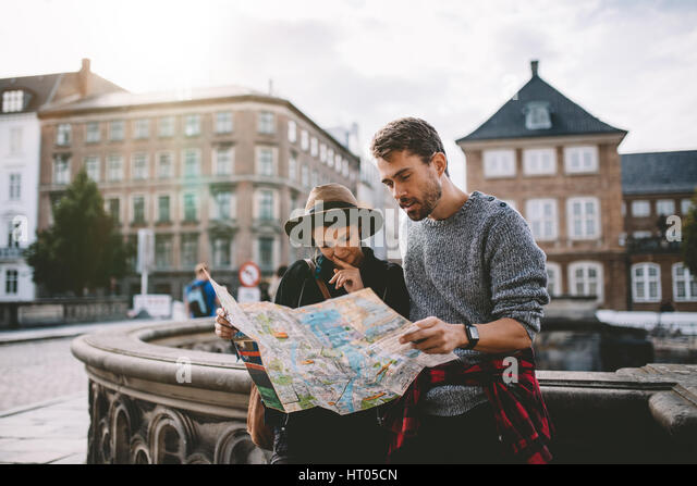 Young couple looking at a navigation map of the city. Tourists finding their way looking at a map standing on the - Stock Image