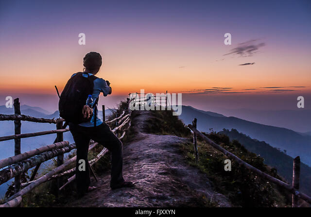 Hiker Standing On Mountain Against Sky During Sunset - Stock Image
